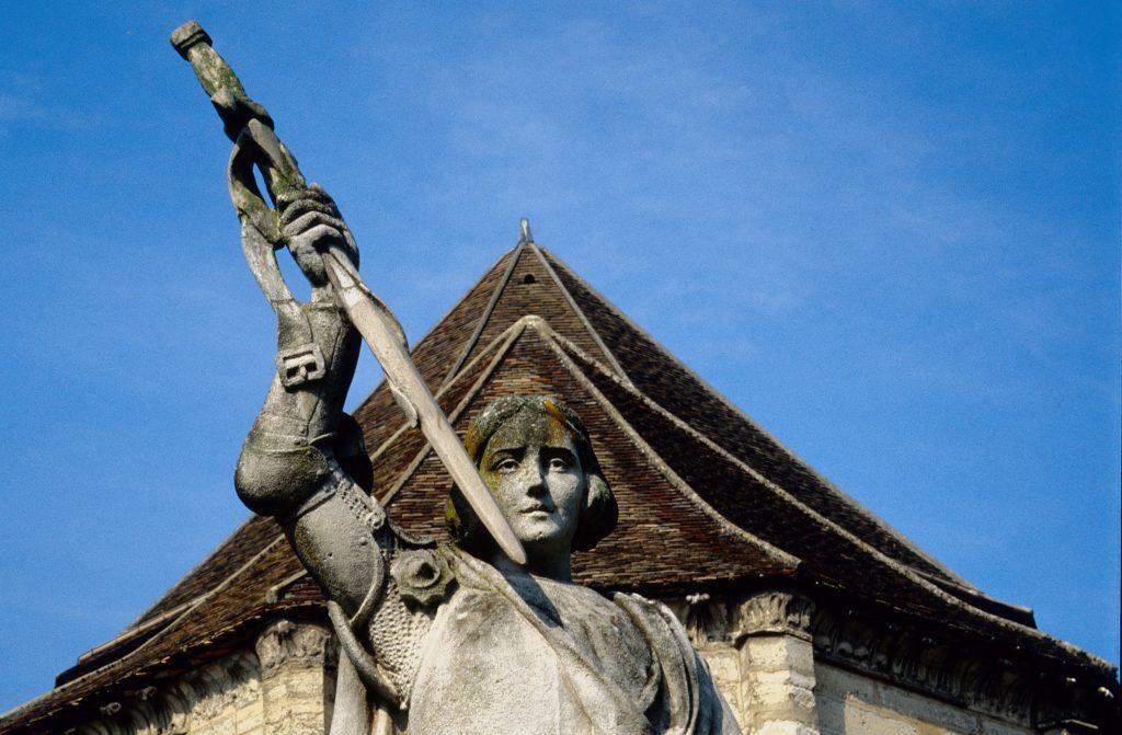 Statue de Jeane d'Arc en armure arbroant son épée devant le chevet de l'abbatiale Notre Dame des Ardents, baptisée en l'hommage du miracle de la Pucelle accompli en ce lieu.